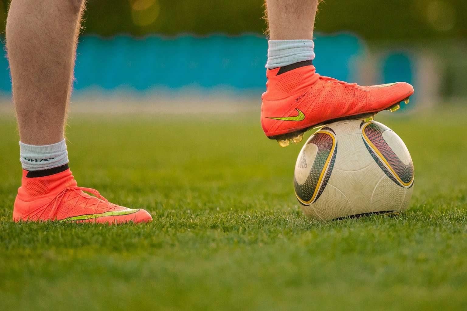 Close up of a person wearing orange soccer cleats with their foot placed on a soccer ball