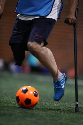 Player wearing a pair of blue soccer shoes while attempting to kick a ball
