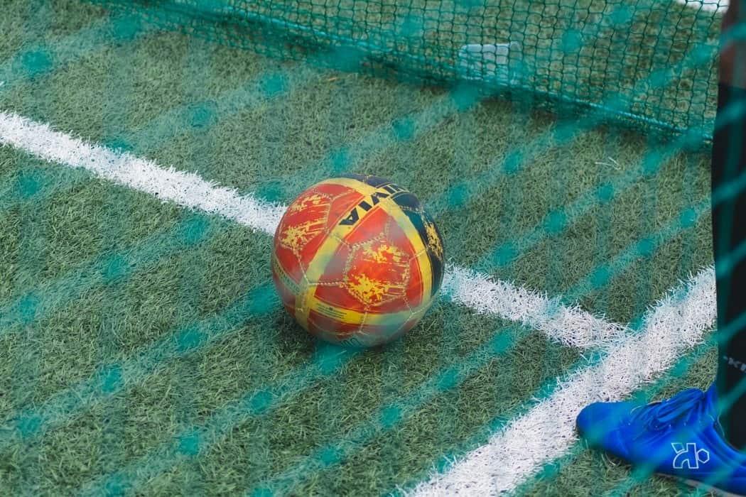 An orange soccer ball lying close to the net