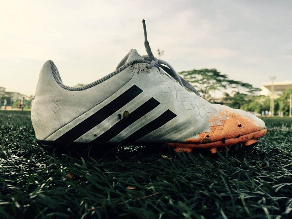 One pair of an Adidas soccer cleat on a grass field