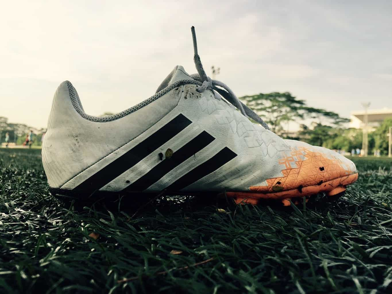 A close up of a rough looking white soccer shoe in a grass field