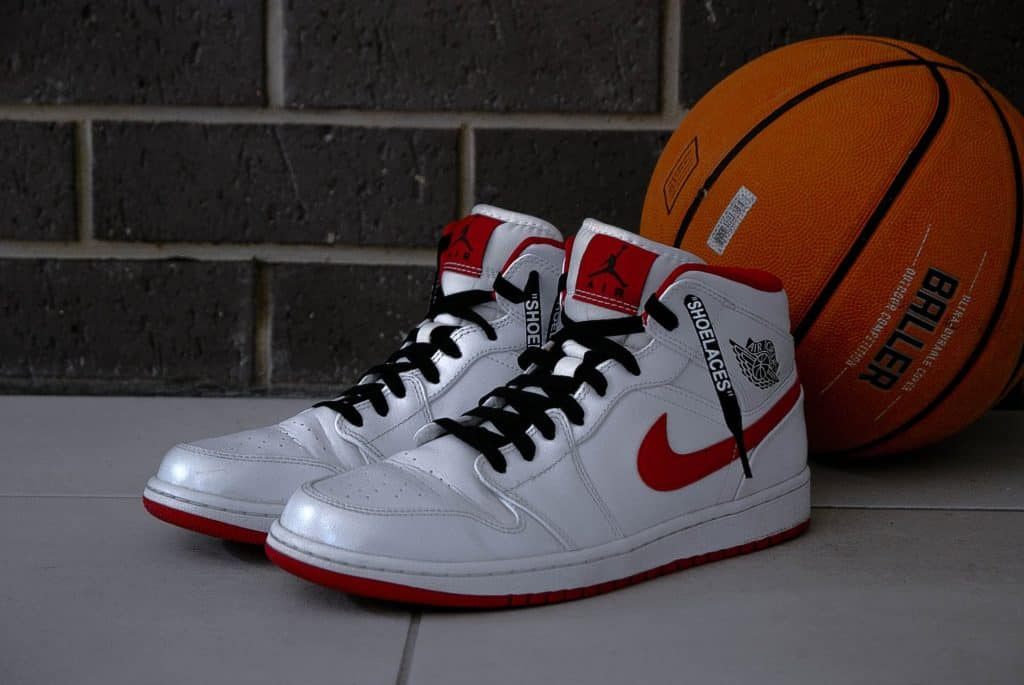 A pair of white and red colored shoes beside a basketball