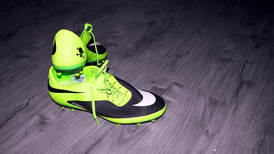 A pair of green and black soccer cleats on the floor