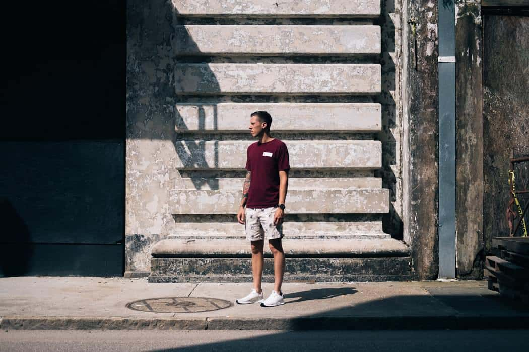 Man standing outside wearing a red t-shirt, shorts and white basketball shoes