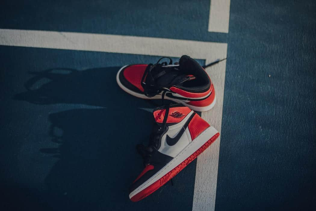A pair of red, white and black Nike basketball shoes placed on a gym floor