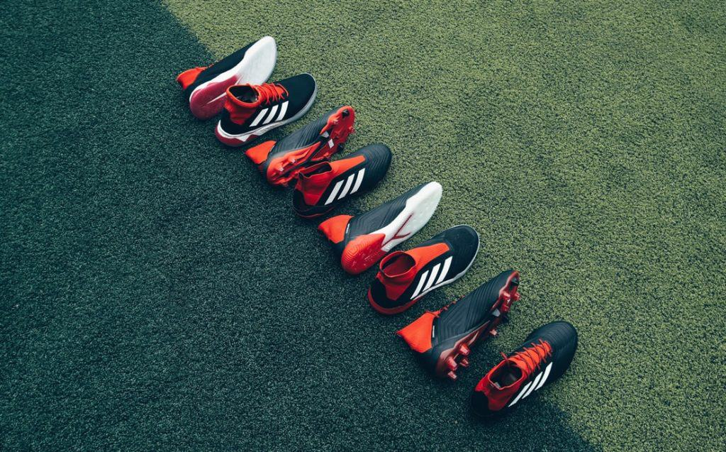 Four pairs of soccer cleats laid on the grass