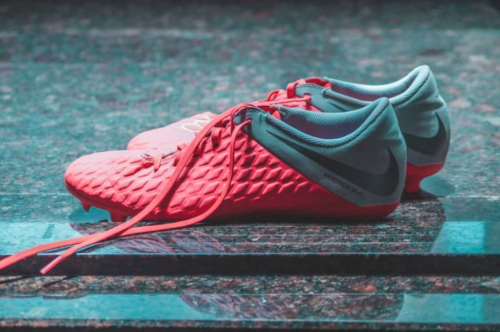 A pair of soccer cleats laid on marble flooring
