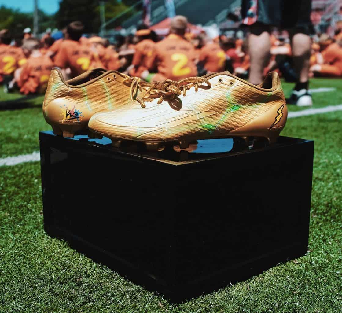 A pair of gold soccer cleats placed on a raised box in a grass field