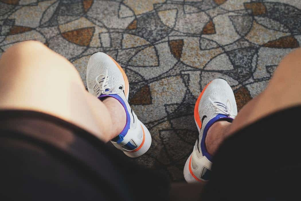 Close up of a person wearing a pair of gray basketball shoes