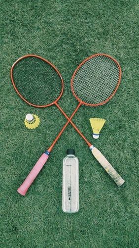Two rackets and two shuttlecocks laid in the grass beside a water bottle