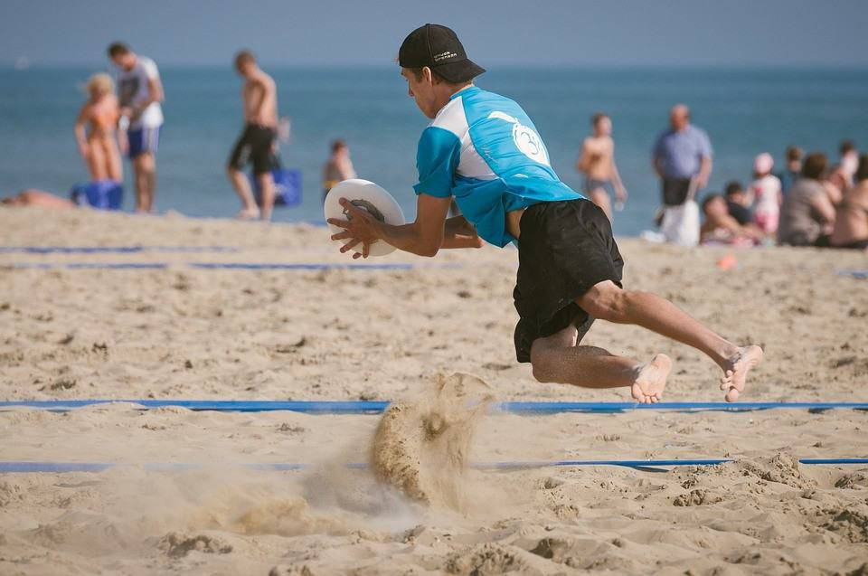 A man playing ultimate frisbee on the beach