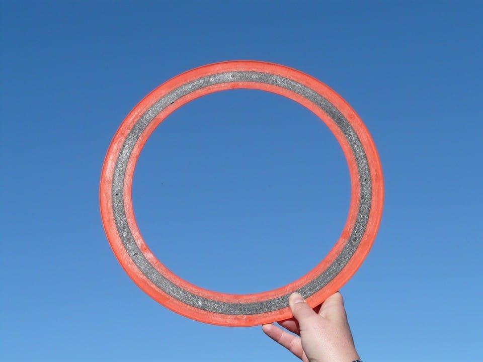 A hand holding an open-center frisbee