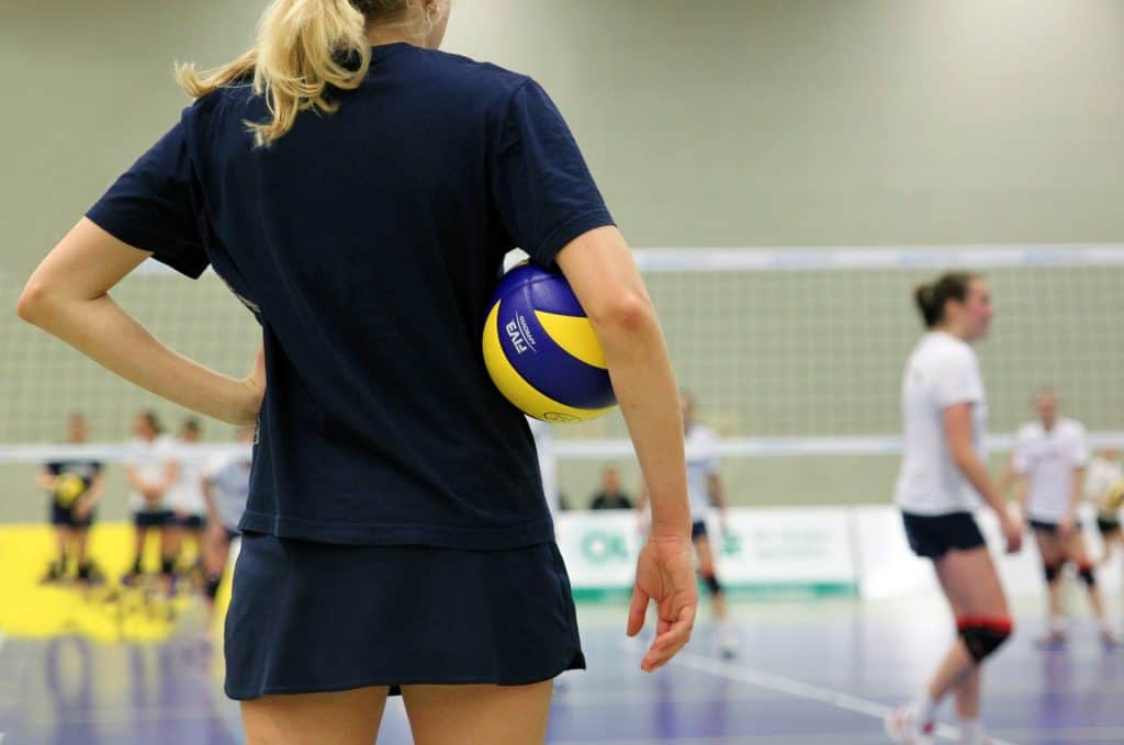 A woman with a volleyball under her arm