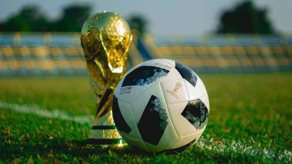 Golden trophy beside soccer ball