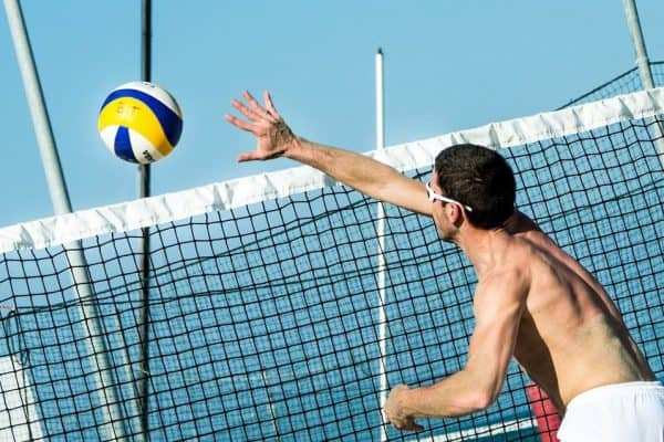 Male beach volleyball player wearing protective sunglasses
