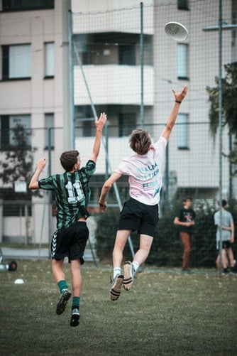 Ultimate Frisbee players trying to catch the disc while wearing their cleats during a game