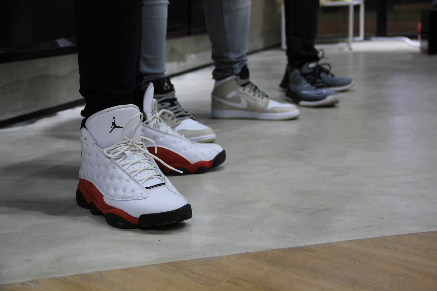 Three people wearing different kinds of basketball shoes