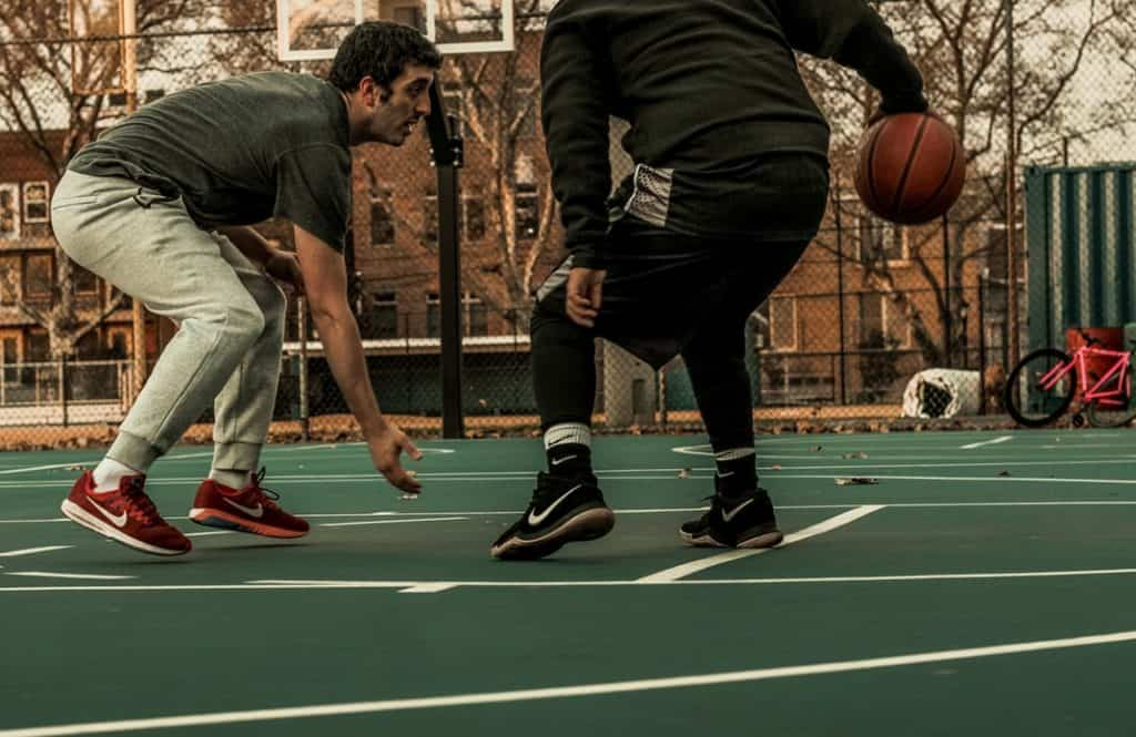 Two men playing basketball in an outdoor court
