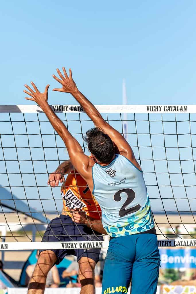 Player near the net trying to keep the ball out in an outdoor volleyball game