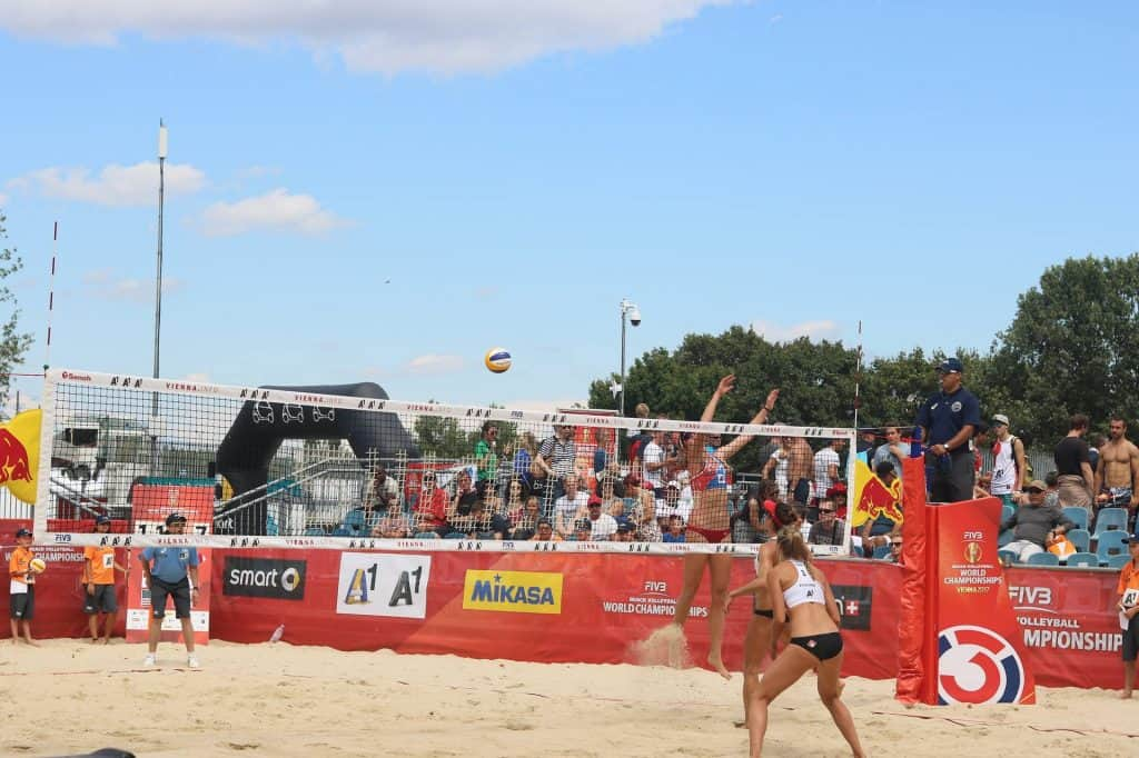 A volleyball game set outside with fans cheering on the players