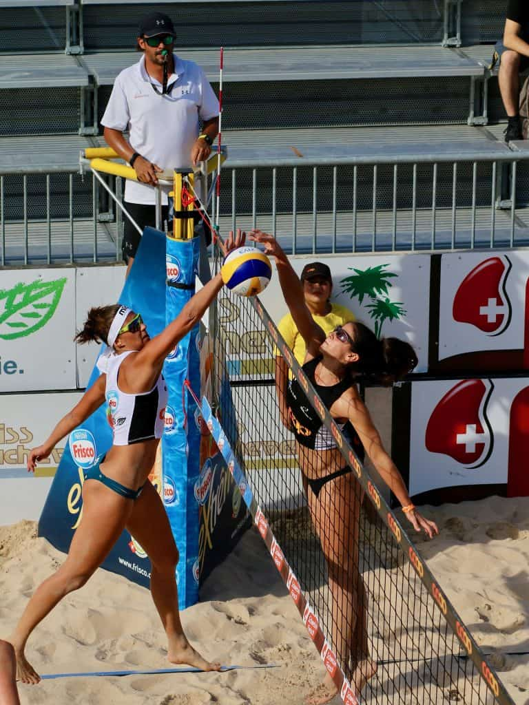 Two players standing near the net trying to block the ball in a volleyball game