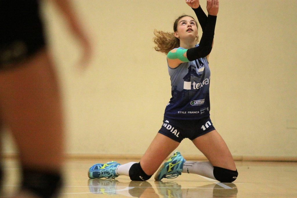 Libero player on her knees trying to hit the ball