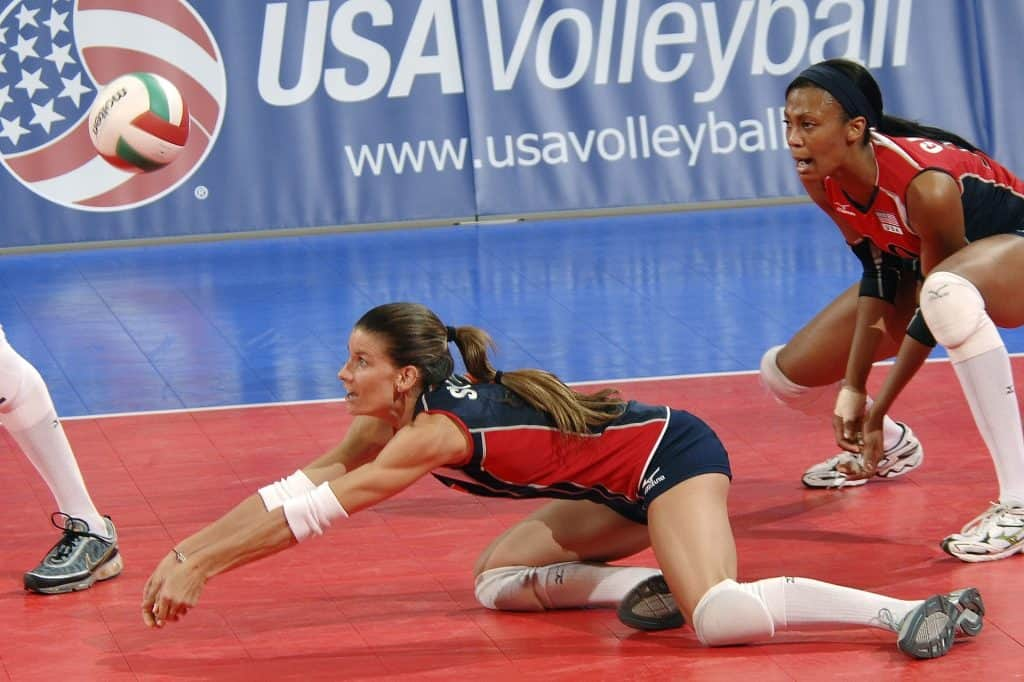 Libero player on her knees on the court trying to save the ball