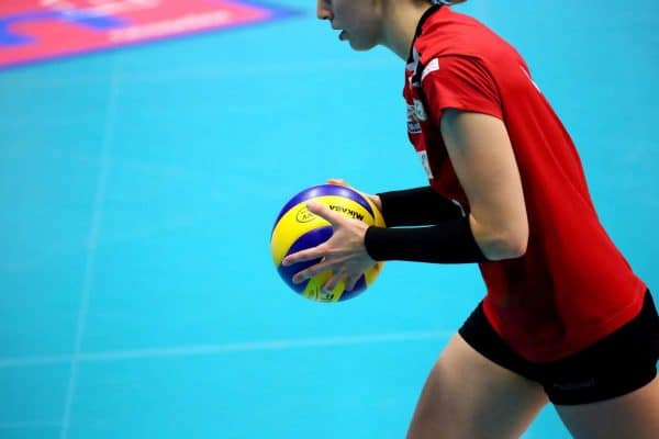 Woman wearing volleyball shorts while holding a ball