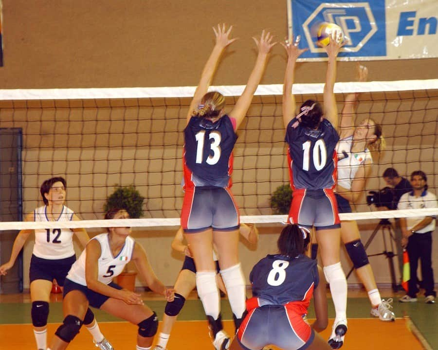 Volleyball players jump to block ball