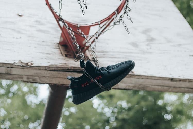 Adidas basketball shoes hanging on a basketball net