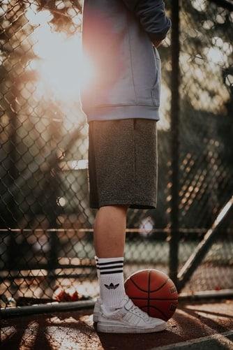 Man standing beside a basketball ball