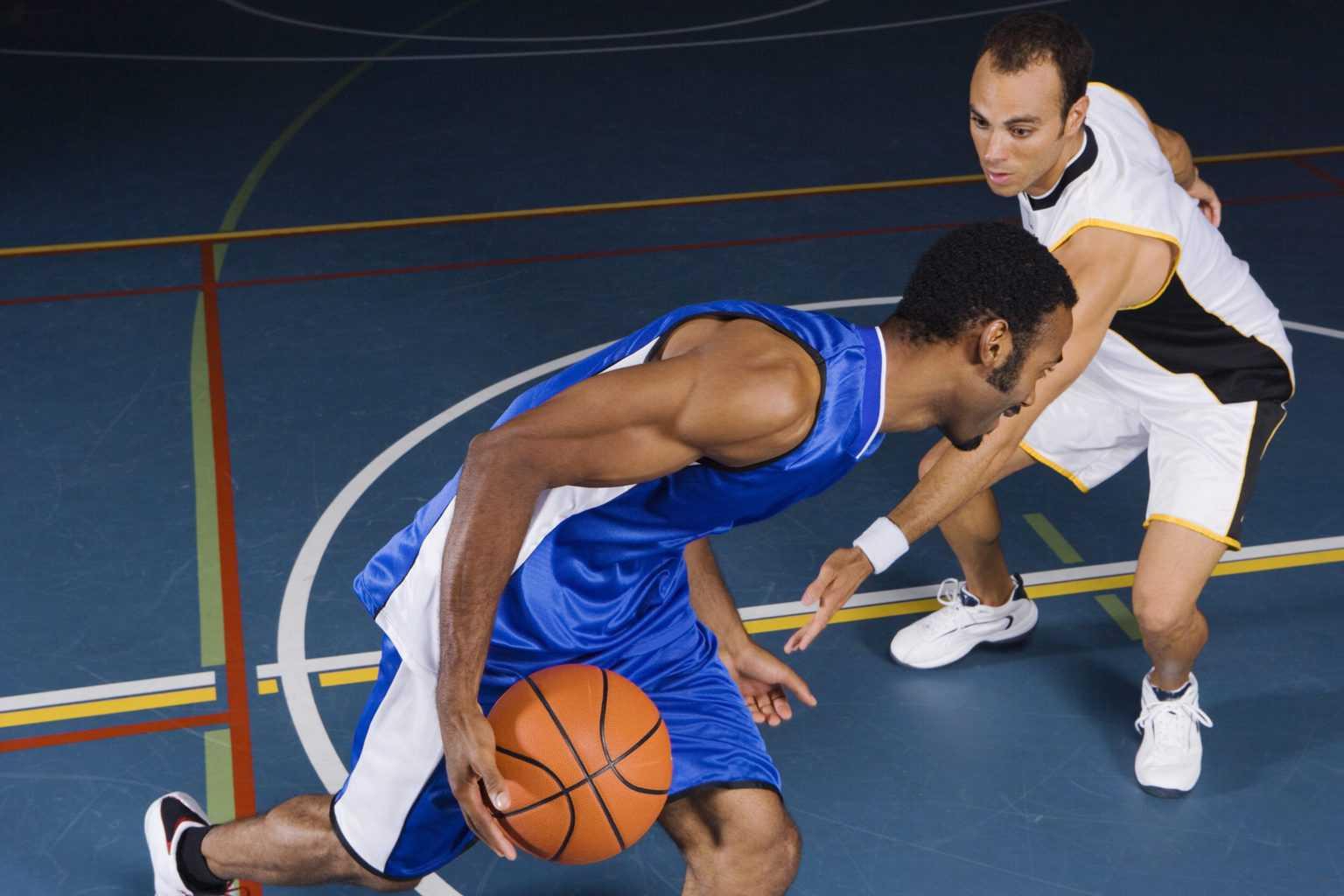 Man dribbling basketball against defender