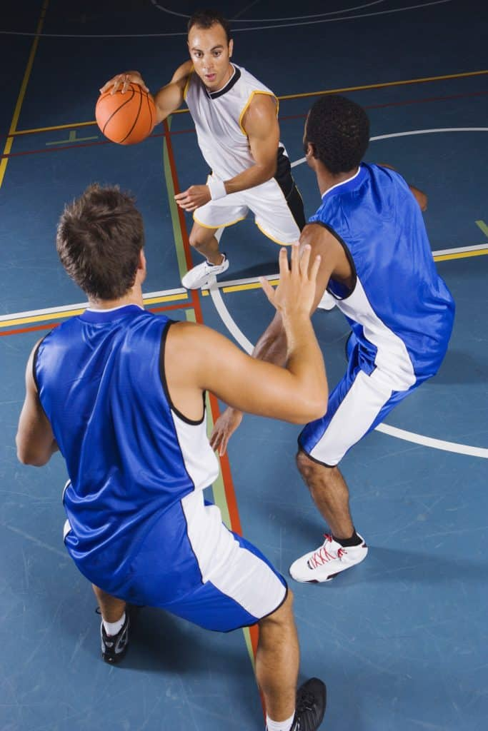 Man dribbling basketball against two defenders