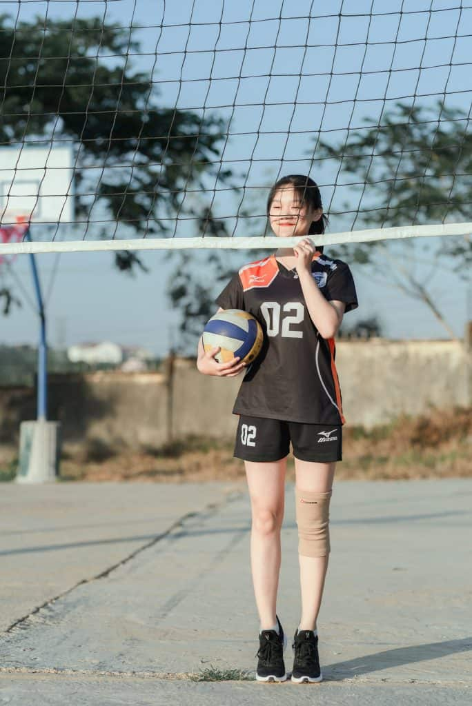 Volleyball player standing beside the net while holding the ball