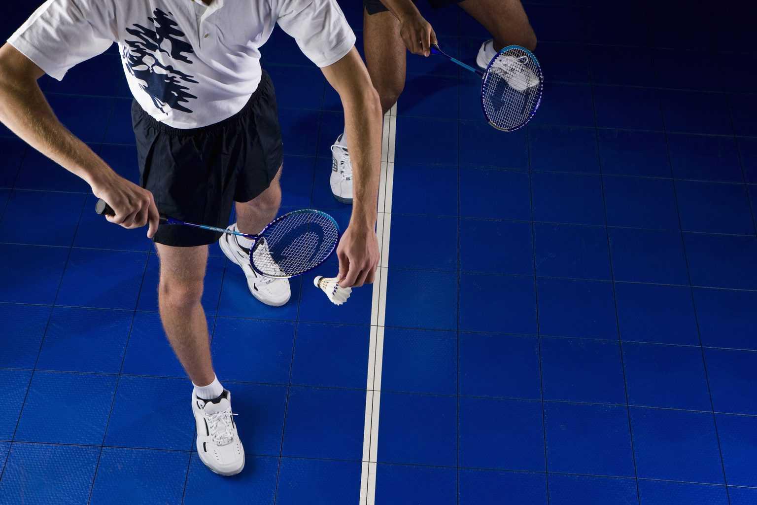 Men playing badminton wearing badminton shoes