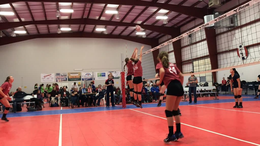 Players trying to block a ball in a volleyball game
