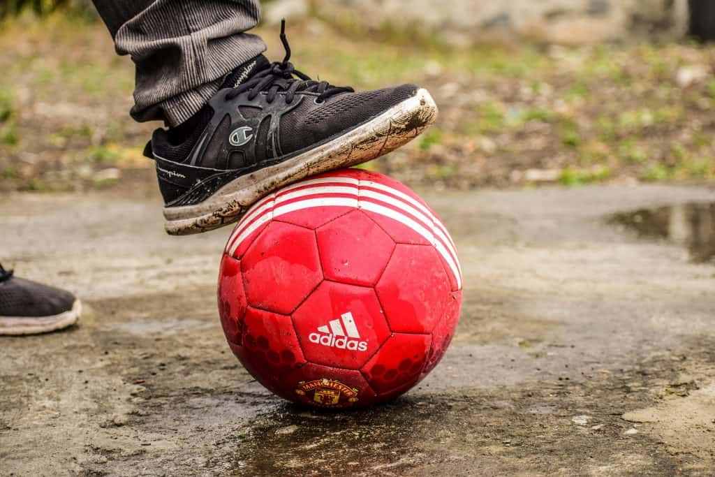 Person stepping on a soccer ball trying to deflate it