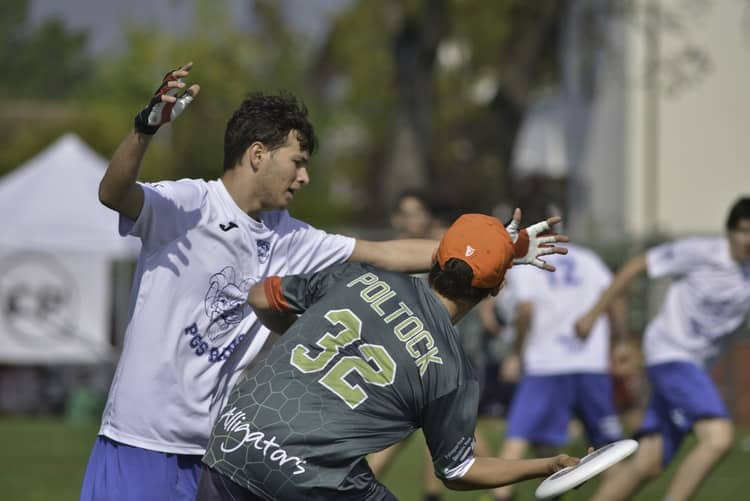 Player trying to block someone from throwing a frisbee disc