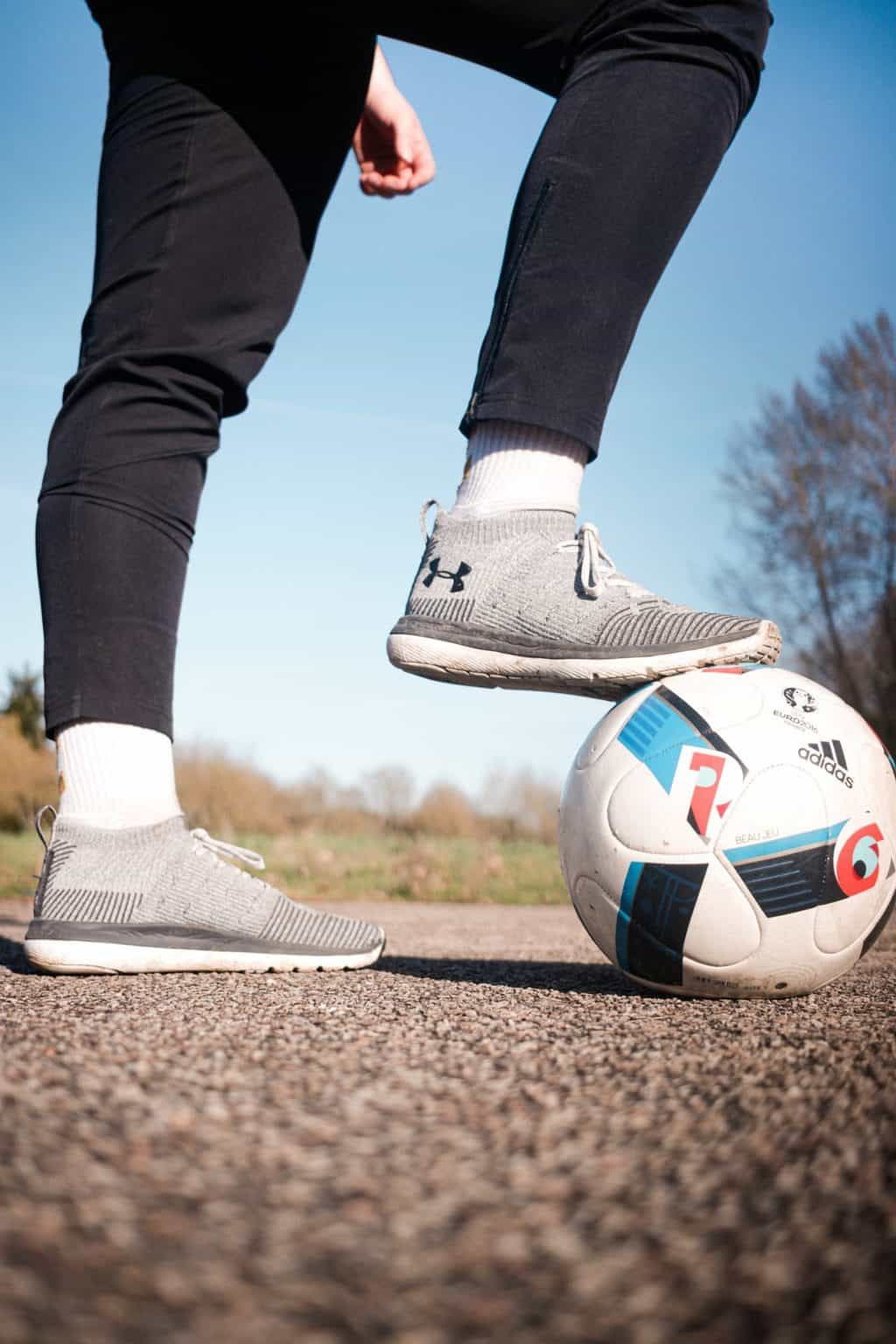 A person stepping on a soccer ball with one foot