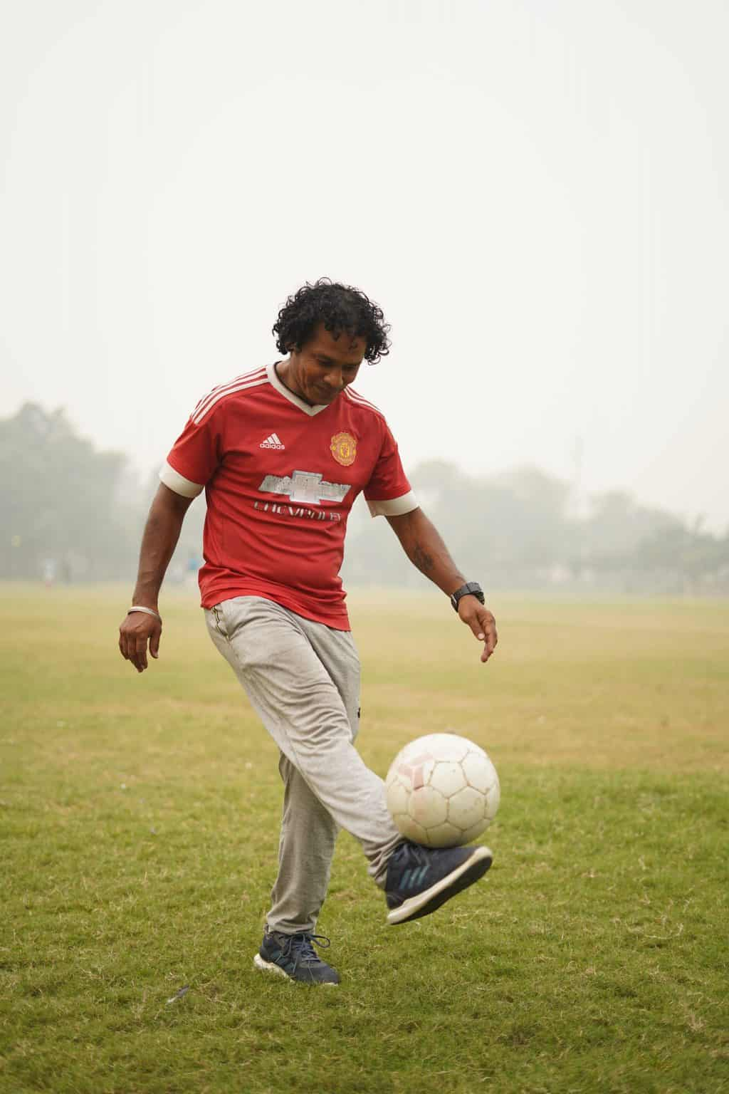 Man practicing soccer in a field