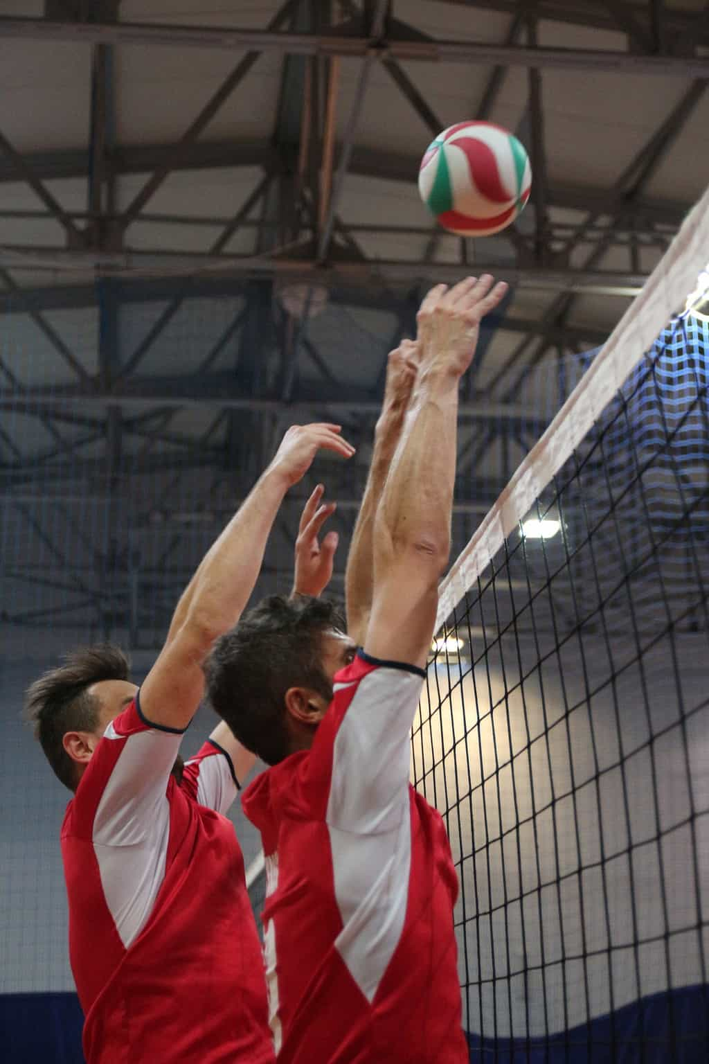 Two volleyball players blocking the ball