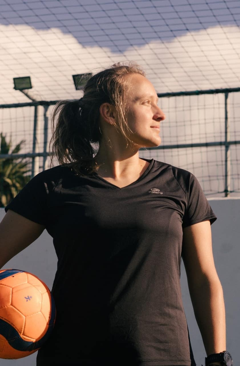 Woman in black shirt holding a volleyball in between her arm and hip