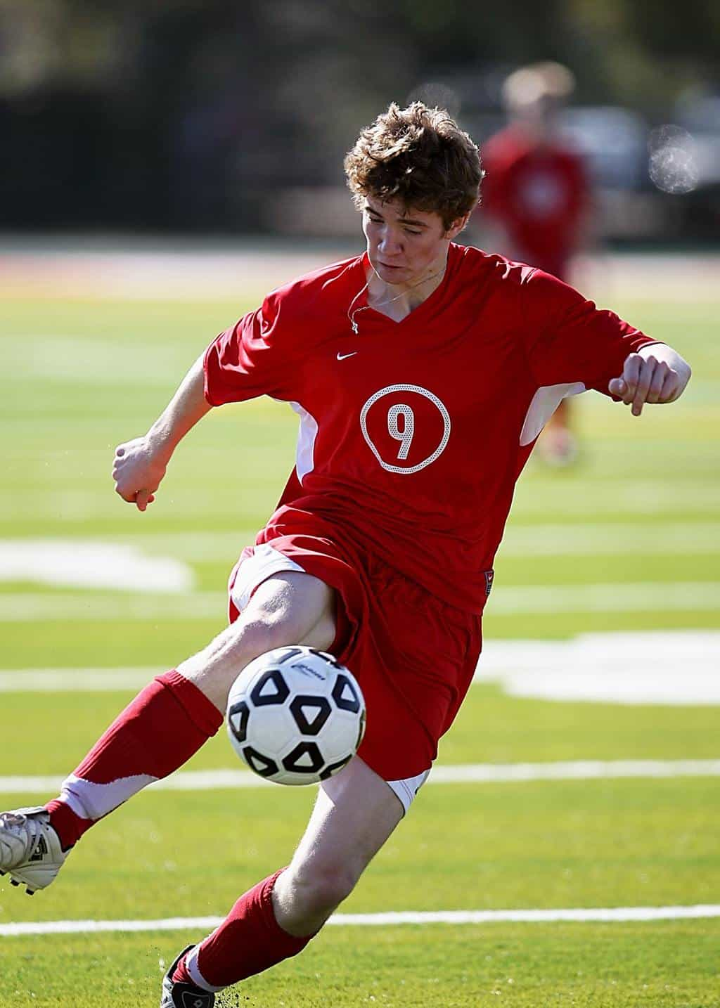 Man in red jersey kicking a soccer ball