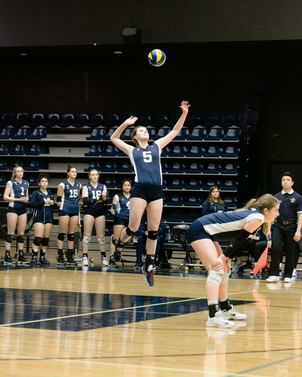 Woman jumping high while hitting volleyball