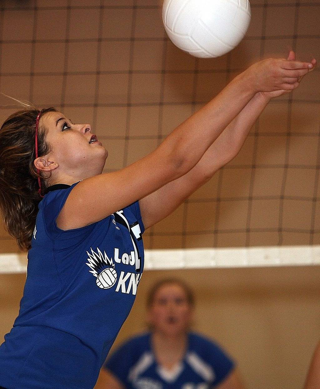 Girl hitting a white volleyball