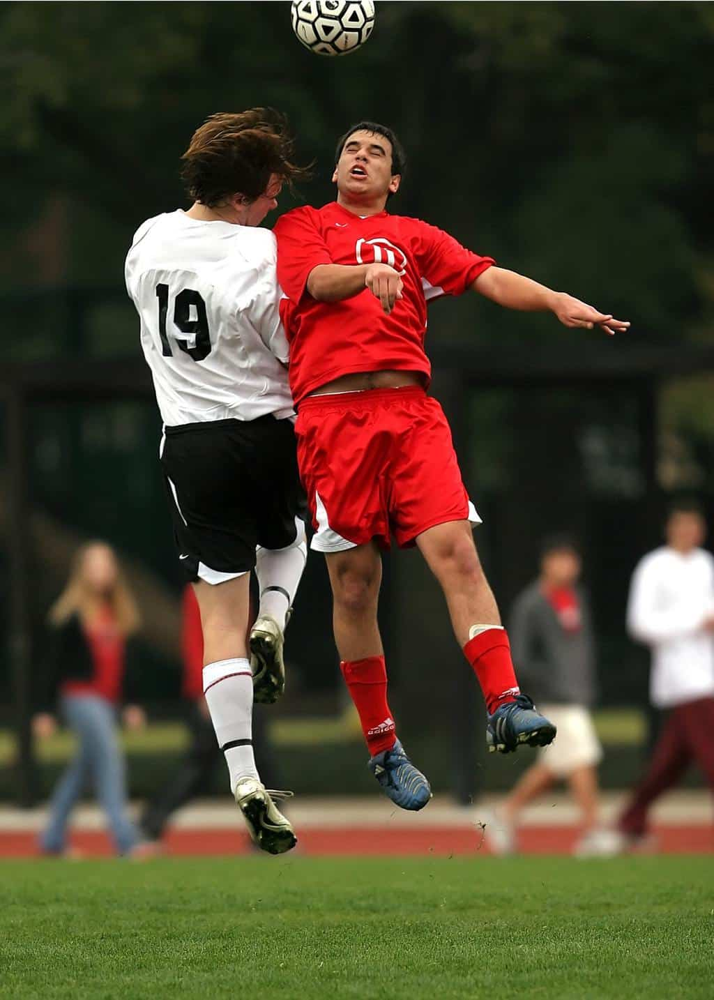 Two soccer players bumping into each other midair
