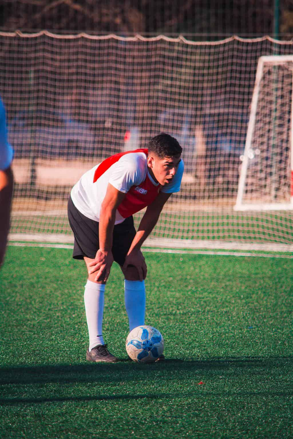 Soccer player resting his hands on his knees