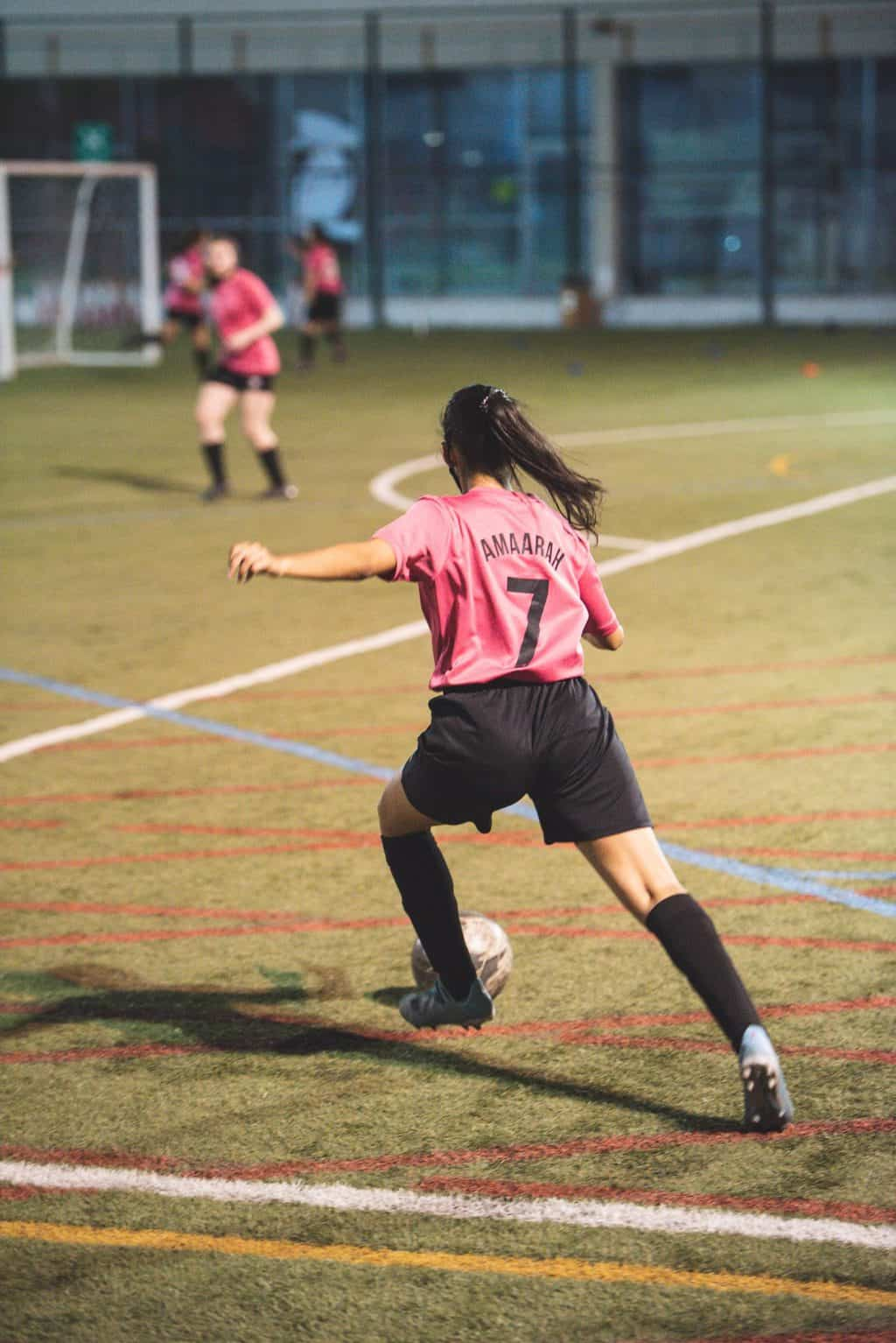 Woman in pink jersey kicking a soccer ball