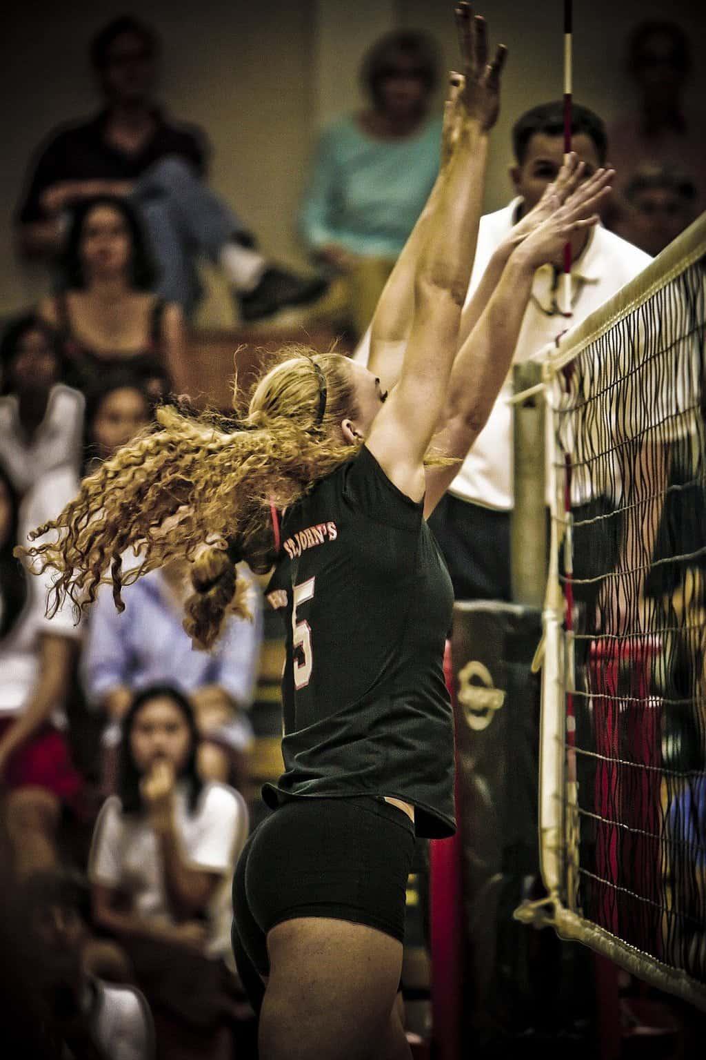 Women volleyball players blocking near the net