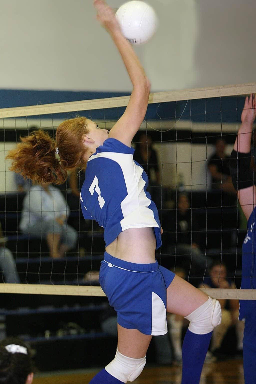 Volleyball player hitting a ball near the net
